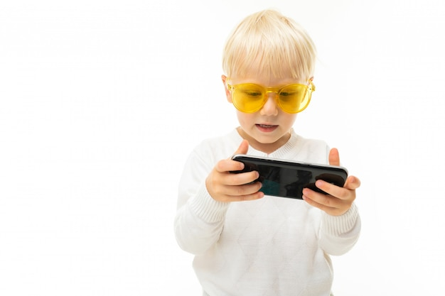 Caucasian blond child plays a game on the phone in a horizontal position on a white background