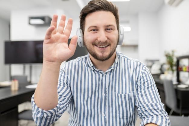 コンピューターで話しているヘッドフォンを持つ白人の金髪の男
