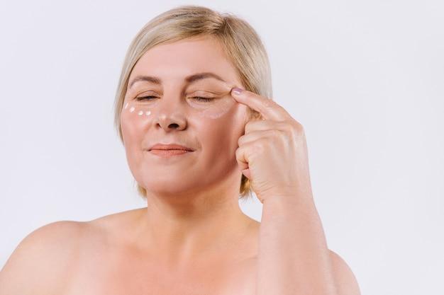 Кавказская белокурая женщина, применяя крем-маску с закрытыми глазами. концепция красоты на белом фоне.
