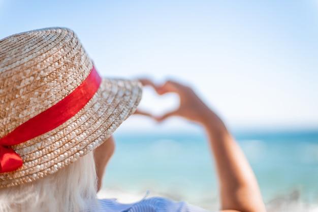 Кавказская белокурая женщина в соломенной шляпе спиной делает любовный знак руками на синем море
