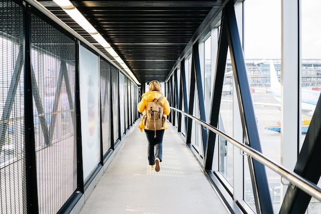 A caucasian blond woman walks through the airport with yellow jacket and backpack