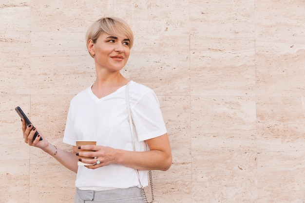 Caucasian blond woman wearing white t-shirt using cell phone, while standing against beige wall outdoor in summer and looking aside at copyspace with takeaway coffee