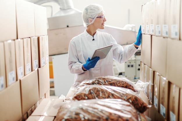 無菌の制服を着た白人の金髪の従業員が立って、製品のロジスティックを扱う。食品工場のインテリア。手にタブレット。