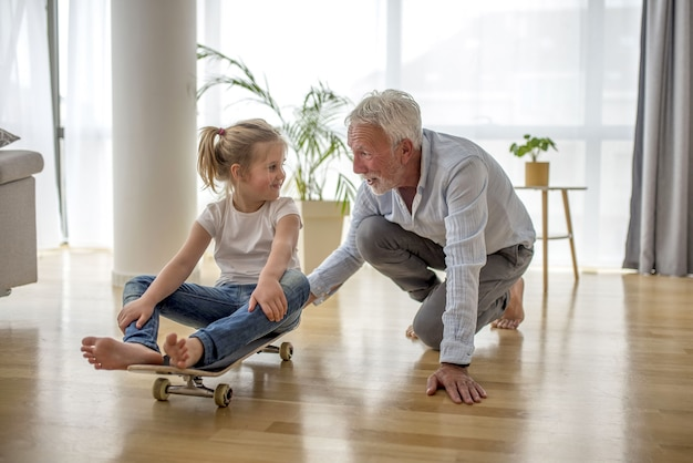 Caucasian blonde female child sitting on skateboard her grandfather pushing her inside a house