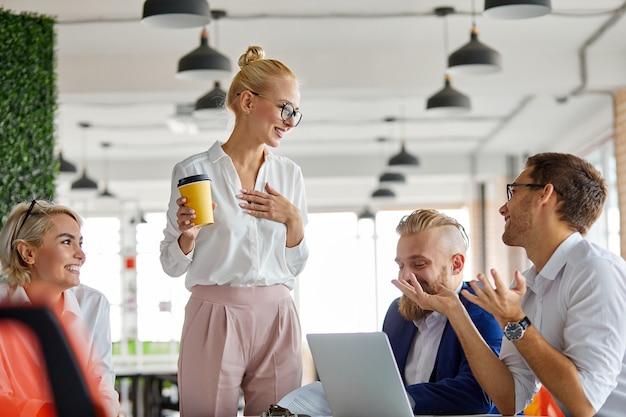 Кавказская блондинка женщина-директор в очках разговаривает с сотрудниками в офисе