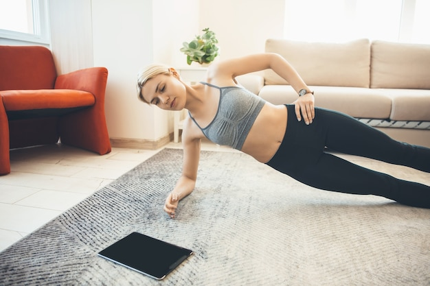 Кавказская блондинка делает упражнения для домашнего фитнеса и в спортивной одежде использует планшет на полу