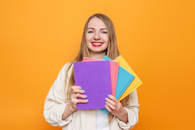 ベージュのジャケットを着た白人のブロンドの女の子の学生は、オレンジ色の壁に分離された笑顔のマルチカラーのカバーで4冊の本を保持しています。英語学校、教育コンセプト