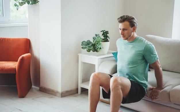 Кавказский блондин тренируется дома без оборудования в спортивной одежде во время фитнеса