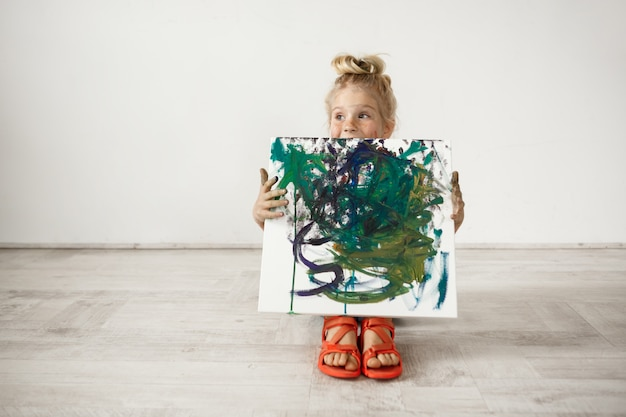 그녀가 그린 그림을 보여주는 백인 금발 유치원 소녀. 사랑스러운 아이가 들고 캔버스. 행복한 어린 시절 개념.