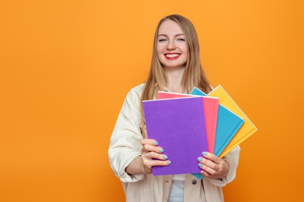 Caucasian blonde student girl holds four books in multi-colored covers smiling isolated over orange background in studio. english language school, education concept