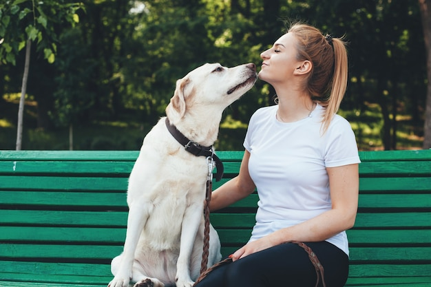Caucasian blonde woman and her labrador are sitting close on bench and kissing during a summer walk in park