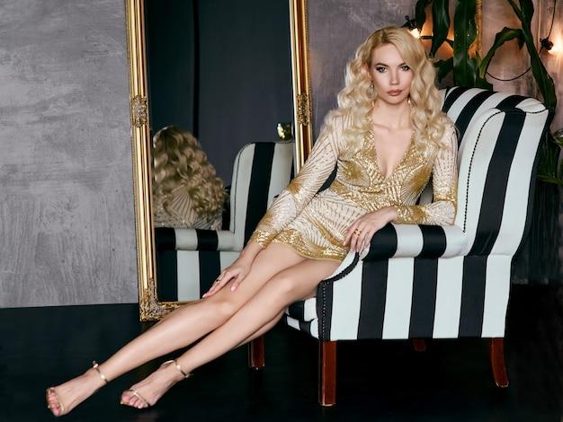 パーティーで肘掛け椅子の黄金のドレスを着た白人のブロンドの女性