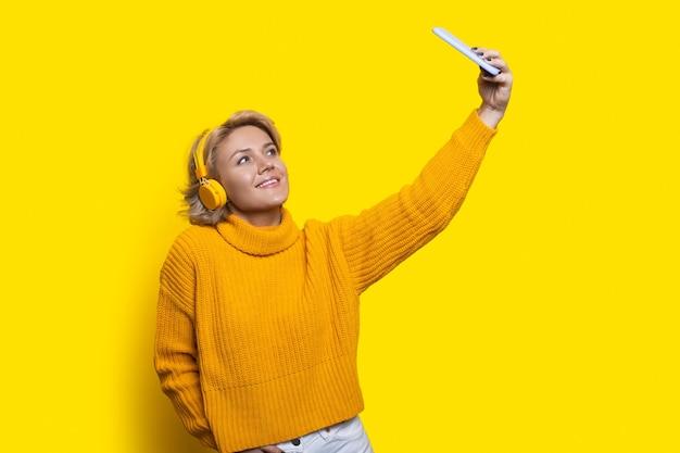 Кавказская блондинка улыбается на желтой стене, делая селфи по телефону и используя наушники