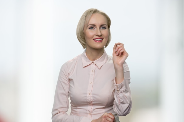 Caucasian blonde woman is touching invisible screen. smiling american lady in white blouse on white background.