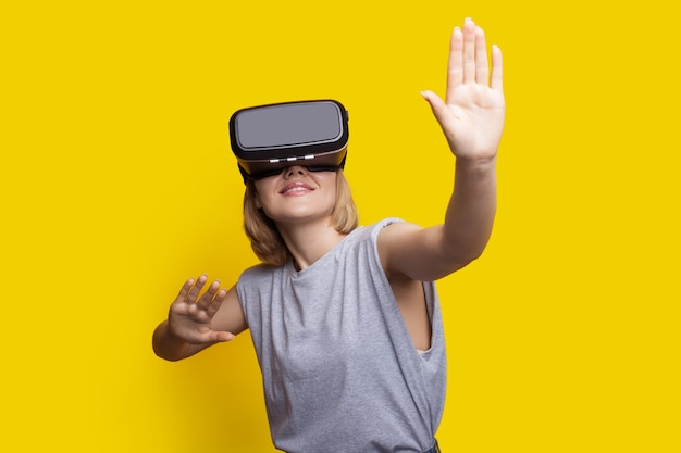 Caucasian blonde woman is touching something while experiencing new augmented reality headset on a yellow studio wall