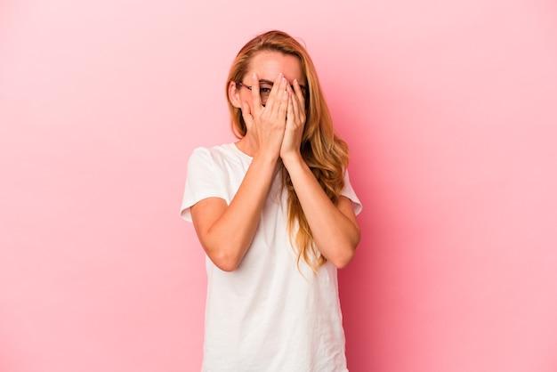 ピンクの背景で隔離された白人のブロンドの女性は、恥ずかしい顔を覆って、指を通してカメラで点滅します。