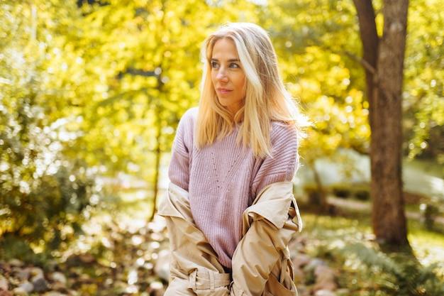 公園を歩いて外の晴れた秋や春の日に幸せそうに笑っている白人のブロンドの女性。