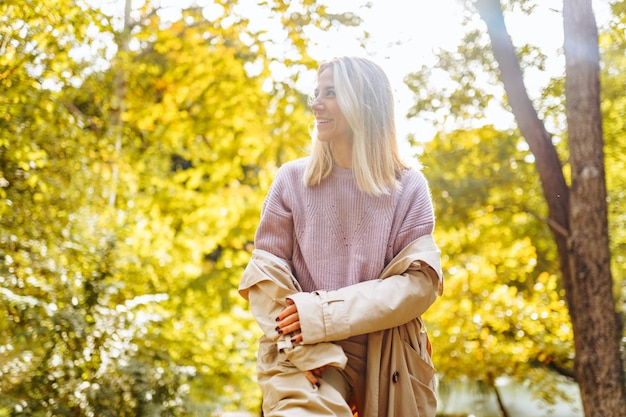 Caucasian blonde woman smiling happily on sunny autumn or spring day outside walking in park.