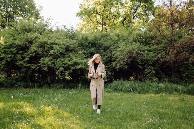 公園を歩いて外の晴れた春の日に幸せに笑顔の白人のブロンドの女性wearindトレンチ