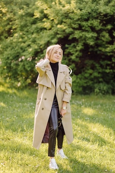 Caucasian blonde woman wearind trench smile happily on sunny spring day outside walking in park