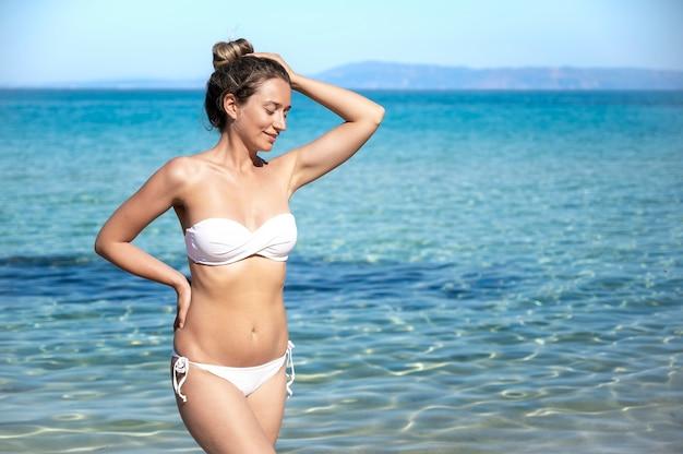 Una donna bionda caucasica in costume da bagno bianco che rimane e che sorride sulla spiaggia del mar egeo, acqua blu in grecia