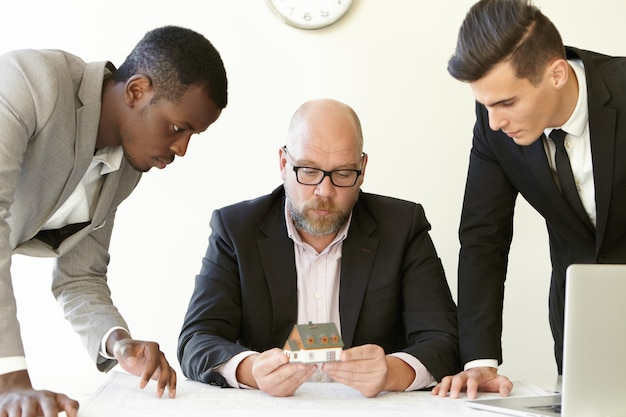 Caucasian boss in glasses holding scale model house of future real estate while two young architects presenting construction project to him.