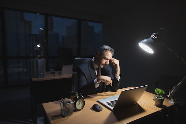 Caucasian boss working late sitting on desk in office at night. business man feeling tired and stress for overload job hold glasses and hand on nose