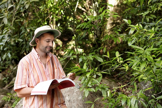 Caucasian botanist or biologist with stuble wearing striped shirt and hat holding notebook in one hand and green leaf of exotic plant in another having joyful expression on his face, enjoying his work