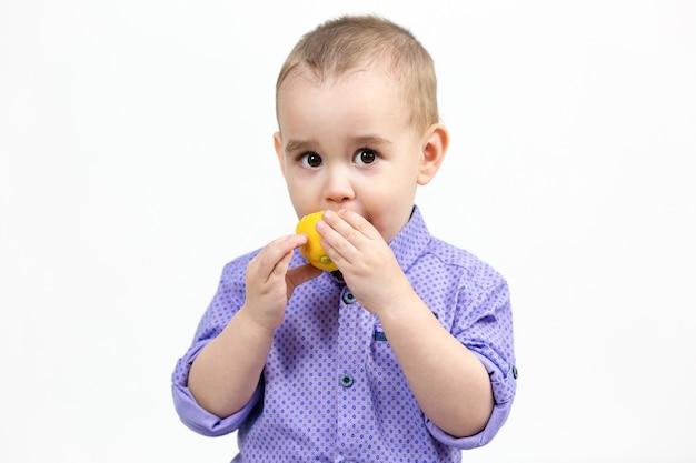 Кавказский мальчик 3 лет ест лимон на белом фоне.