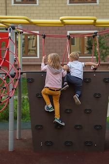 白人の男の子と女の子が遊び場のクライミングウォールを登る