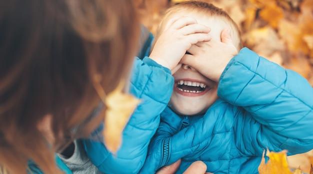 秋の葉と地面で遊んでいる白人の少年と彼の母親は、口を開けて笑っている