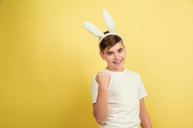 黄色のスタジオの背景にイースターバニーとして白人の少年。ハッピーイースターのご挨拶。