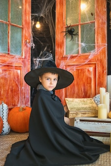 Caucasian boy in carnival wizard costume reading magic book on halloween decor background