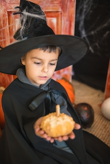 Caucasian boy in carnival wizard costume with decorative pumpkin on halloween decor background