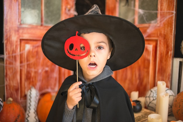 Caucasian boy in carnival wizard costume with paper pumpkin on halloween decor background