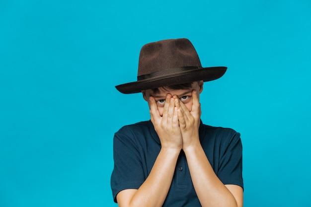 暗い青色のtシャツとつばのある帽子を着た白人の少年が恥ずかしがり屋の表情で手で顔を覆い、笑みを浮かべて彼の指を通して見える