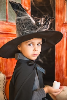 Caucasian boy in farytale carnival wizard costume holding candle in hand, looking at camera on halloween decor background