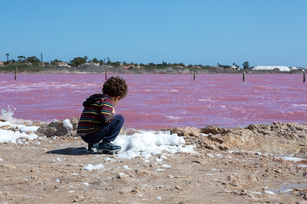 Caucasian boy of five years with curly hair observing the natural phenomenon of the pink lake located in the city of torrevieja alicante spain
