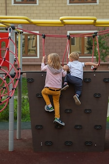Caucasian boy and a girl climb the climbing wall in the playground