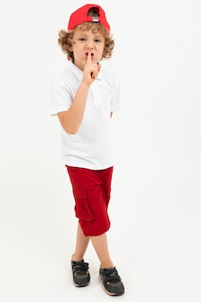 Кавказский мальчик в белой футболке, красной шапочке, красных шортах советует хранить молчание на белом фоне