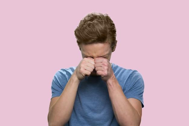 白人の男の子が泣いています。ピンクの背景に分離されたtシャツの悲しいティーンエイジャー。
