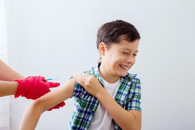白人の少年は腕に予防接種を受け、子供は背を向けて恐れています。