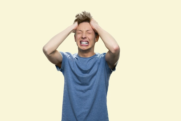 Caucasian boy is having nervous breakdown. handsome casual-dressed guy is pulling his hair in despair. isolated on white background.
