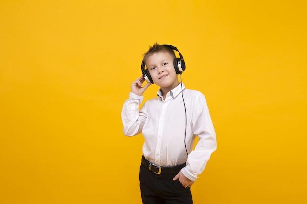 Caucasian boy listening music studio concept, yellow surface. isolate