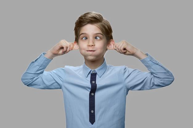 Кавказский мальчик делает лицо обезьяны. закройте вверх по мальчику смешной ребенок морщась сером фоне.