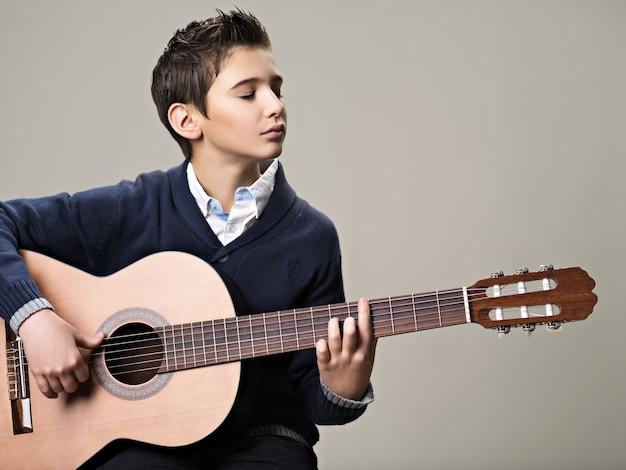 アコースティックギターで遊ぶ白人の少年。