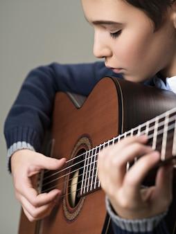 Кавказский мальчик играет на акустической гитаре.