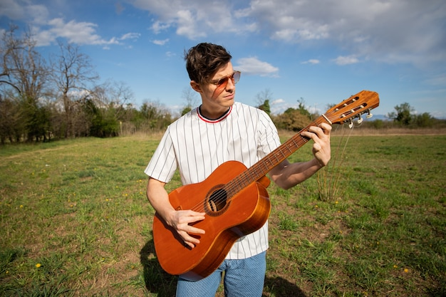 Caucasian boy plays the guitar outdoors in a field musician plays an instrument