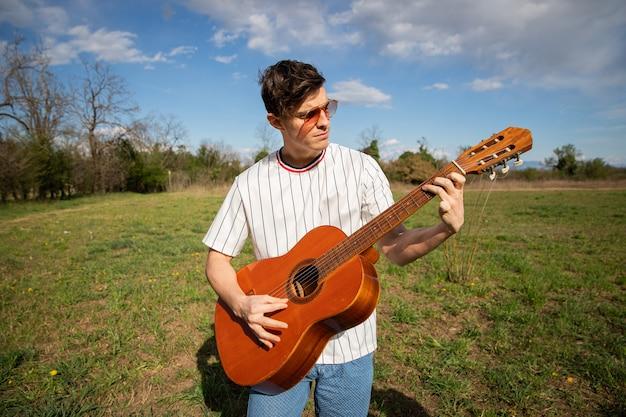 白人の少年が野外でギターを弾くミュージシャンが楽器を弾く