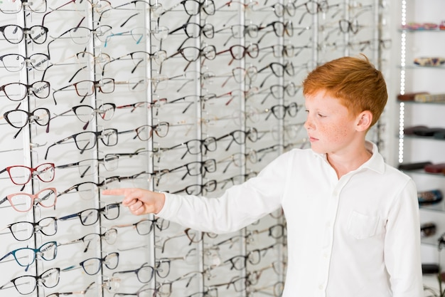 Caucasian boy pointing index finger at eyeglasses rack
